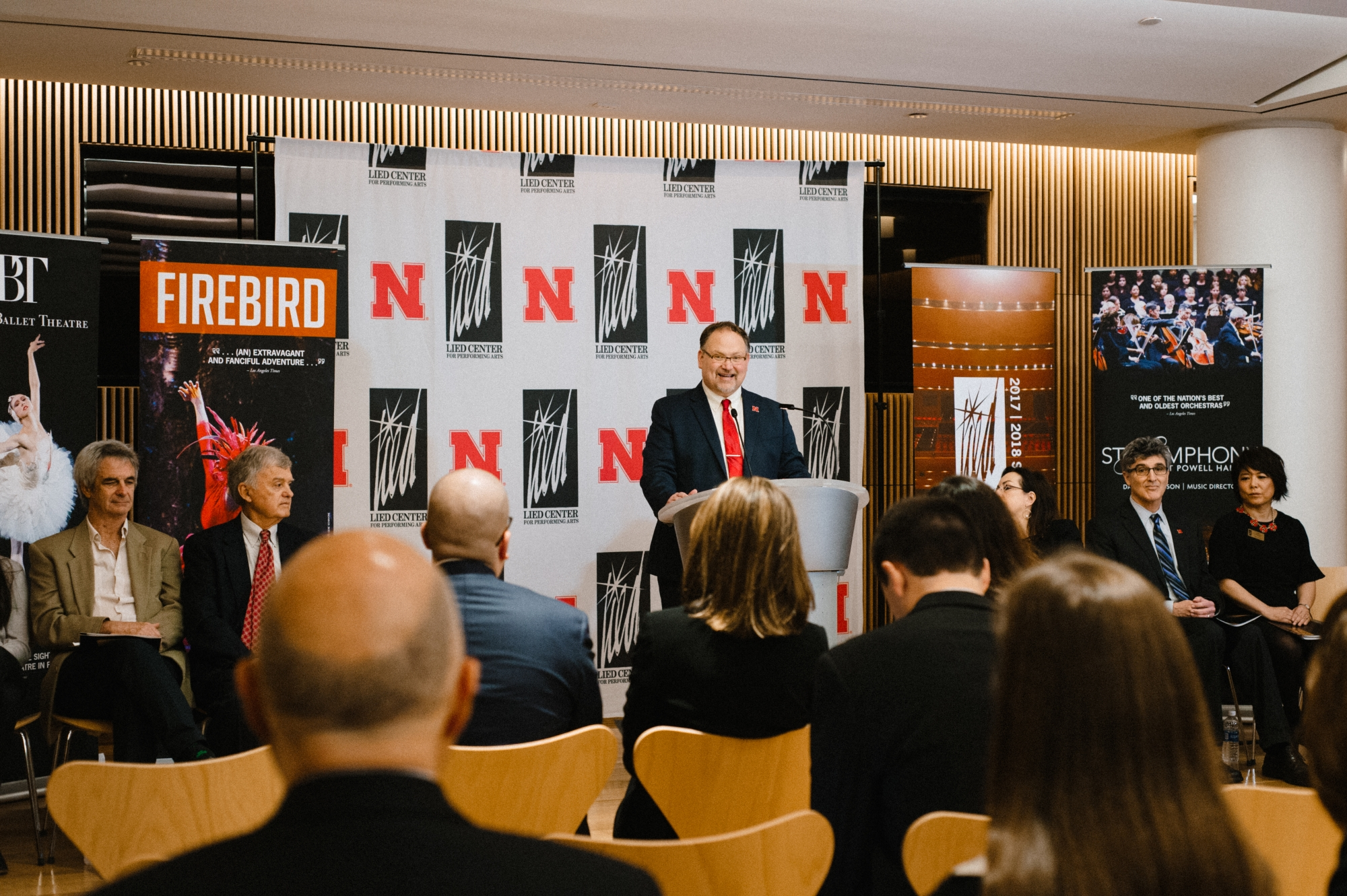 Image of the press conference announcing the Firebird performance showing Bill Stephan at the podium in front of the Lied Center and University of Nebraska backdrop