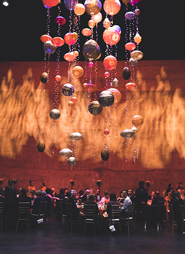 Image of the elaborate decorations with various shapes hanging from sparkly strings above the stage where guests enjoy dinner during the Friends of Lied Fire and Ice gala