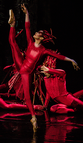 "Image of Misty Copeland dressed all in red dancing ""Firebird""  in front of two other performers in red seated on the stage"