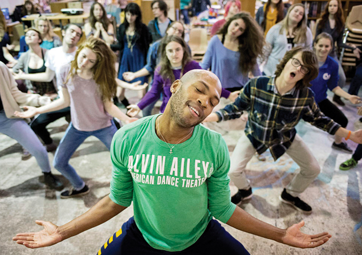 Image of a dancer in a green Alvin Ailey T-shirt facing the camera leading a dance master class for UNL students behind him
