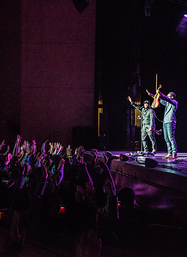 Image of UNL students in the audience applauding and the performers from Black Violin waving to the crowd