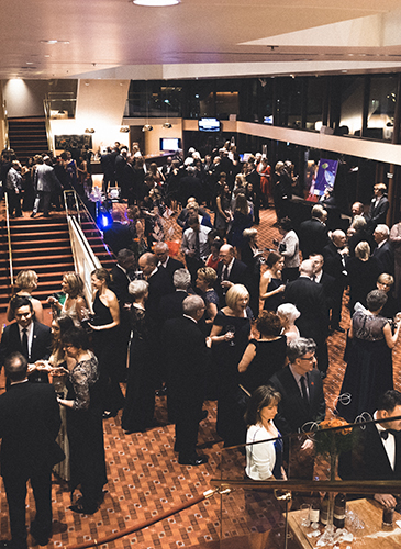 Image of the Lied Center Orchestra Lobby filled with dozens of partygoers in fancy dress enjoying cocktails before the Friends of Lied gala