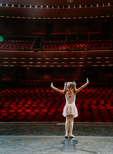 Image taken from the stage looking out into an empty Lied Center hall showing a little girl in a ballerina outfit dancing.