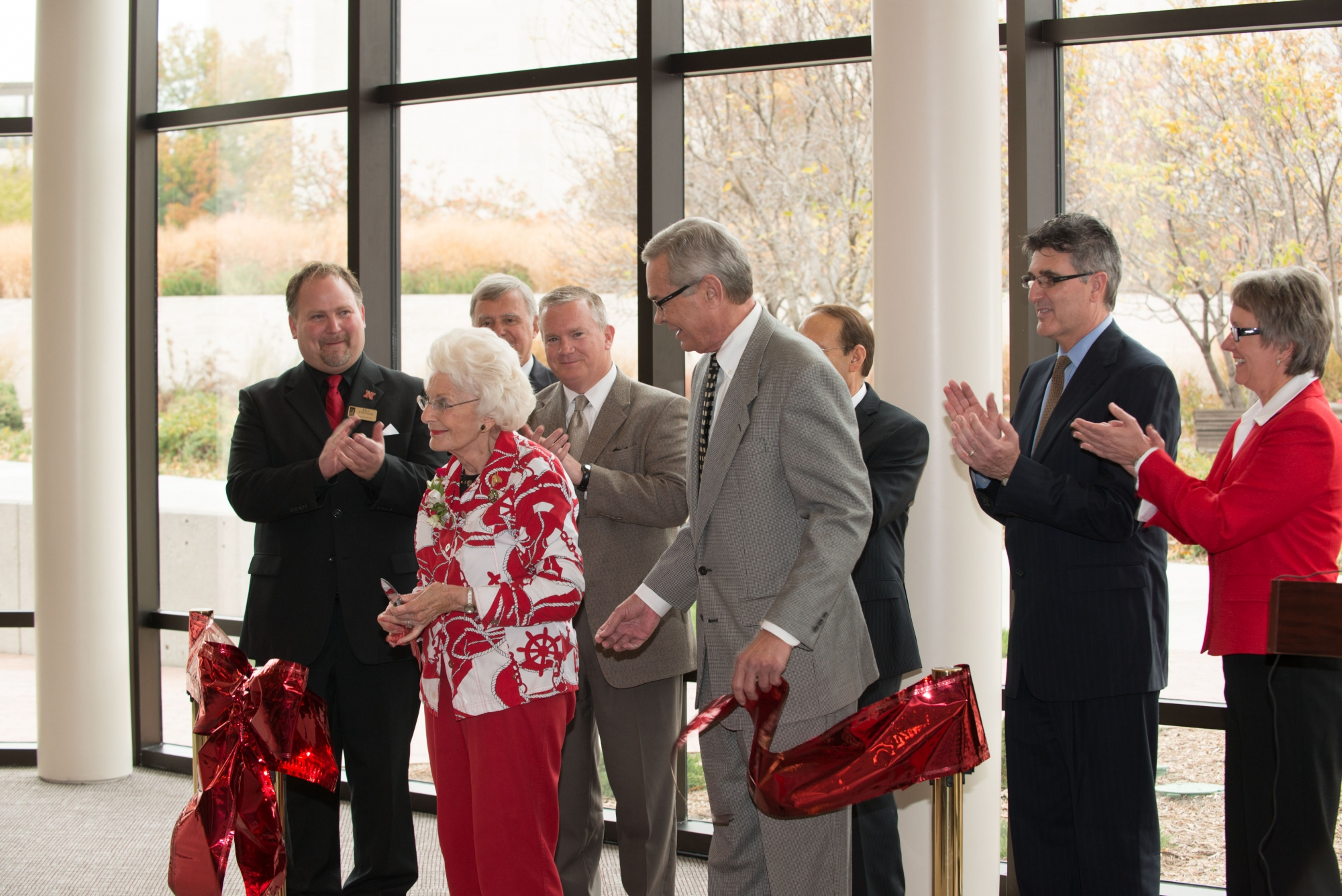 Image of the ribbon cutting for the Lied Commons building showing Christina Hixson, the Mayor of Lincoln, and other dignitaries applauding after the ribbon is cut.