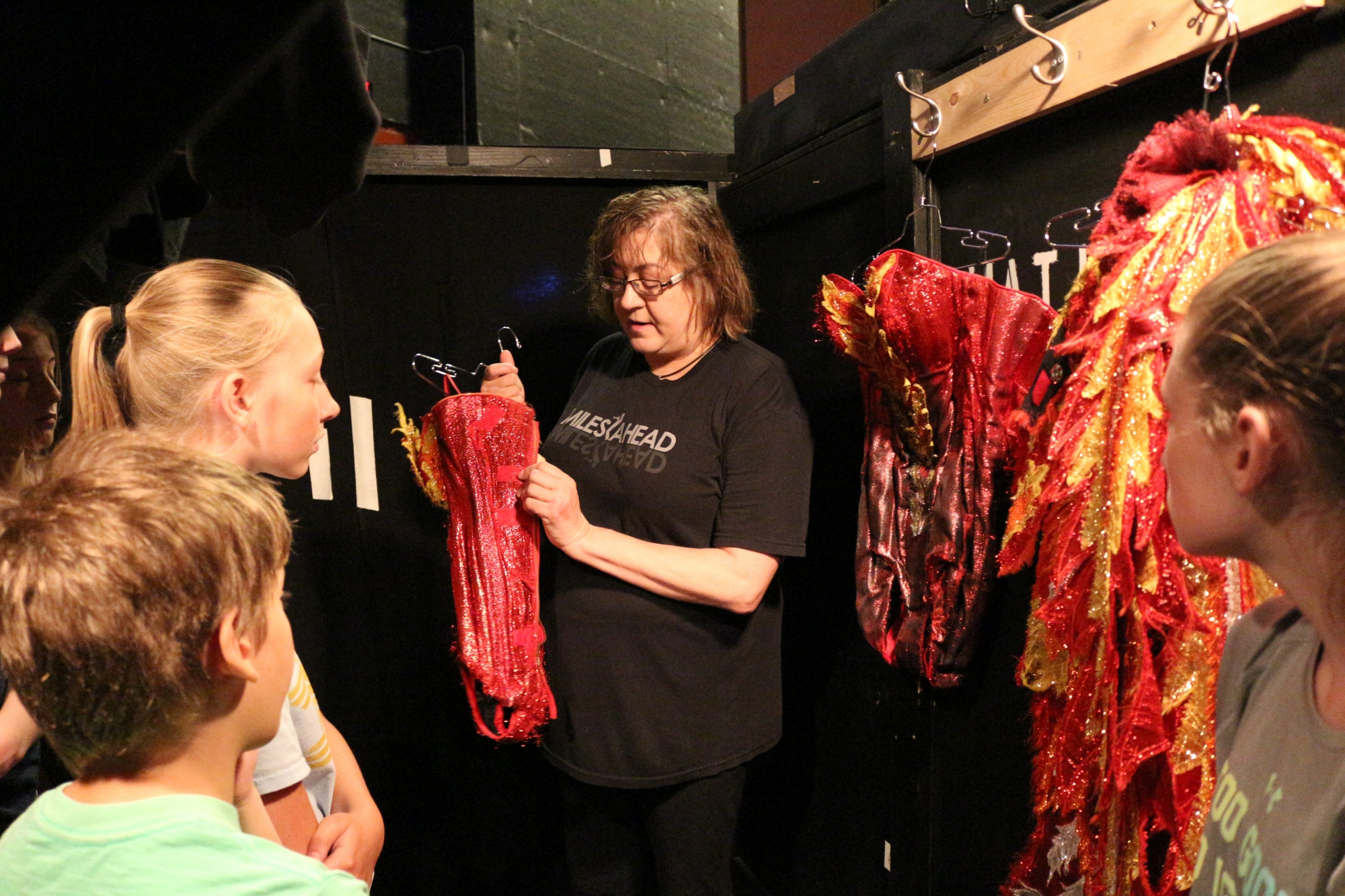 Image of the costume designer showing off red costumes to fashion design students