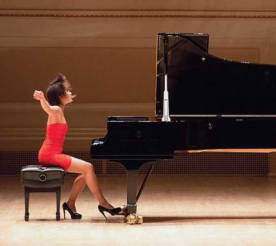Image of Yuja Wang seated at a piano with arms raised and hair flying forward