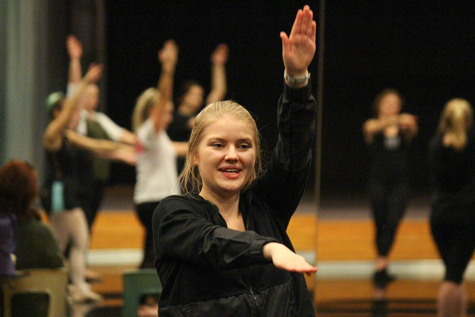 Image of a UNL student with her right arm raised and left arm pointing forward during the Trinity Irish Dance master class