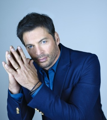 Harry Connick Jr wearing a navy jacket against a light blue background.
