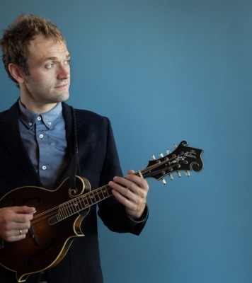 Chris Thile performs on mandolin wearing a collared shirt and sweater against a blue background.