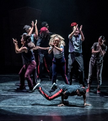 Man wearing black break dancing and surrounded by a group of people wearing black and red who are clapping in front of a black background
