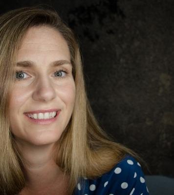 Photo of Jana Eggers in a blue shirt against a dark background.