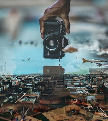 An image of a black camera photoshopped above a town.