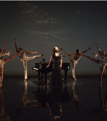 Woman in black, sparkly dress looking up standing in front of a piano. She is surrounded by six dancers dressed in white, all in front of a black background.