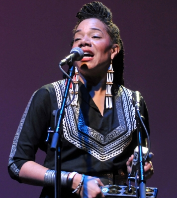 Woman wearing a black top singing into a microphone while playing a percussion instrument in front of a purple background.