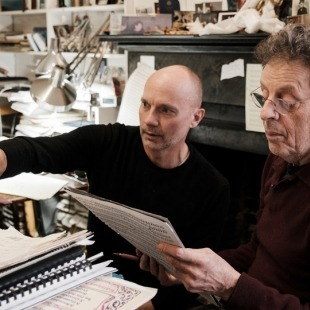 Image of Philip Glass and Paul Barnes collaborating at a piano
