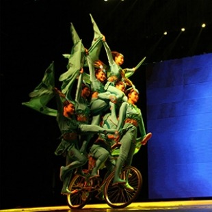 A group of six or more acrobats in chinese costumes all balanced on a single bicycle riding around the stage in front of a blue background