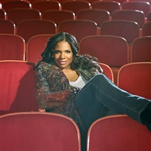 An image of Audra McDonald sitting in red theater seats.