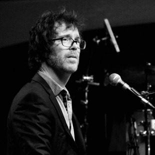 Candid black and white photo of Ben Folds sitting at his piano