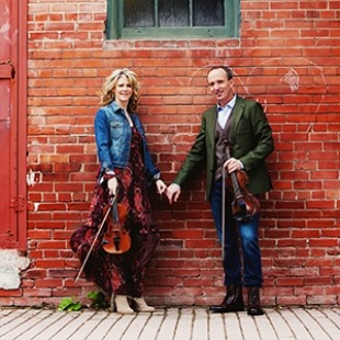 Image of the two performers from Celtic Celebration holding hands and their fiddles while standing in front of a brick wall.