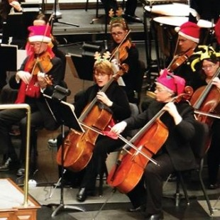 Orchestra members play their instruments dressed in Christmas costume