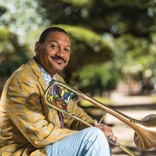 Delfeayo Marsalis wearing a gold jacket, sitting outside by some trees, holding his trombone.
