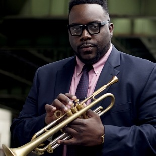 Man in a blue suit and a pink/mauve shirt holding a trumpet in front of a green and grey background.