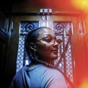 Woman in a grey sweater looking over her shoulder to the camera standing in an old elevator with an orange/red flare along the right side of the picture.