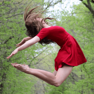 Image of female dancer in red dress. She is jumping in the air bending her arms and legs together behind her back. There is a backgound of forest trees behind her.
