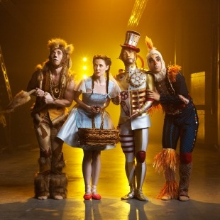 Man in lion costume, woman in blue dress and red shoes, man in tin man costume, and man in scarecrow costume standing next to each other in front of a yellow background.
