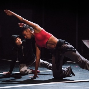 Woman in red top and grey pants on one hand and one knee reaching over her head with a person in black behind her mimicking her all in front of a black background.
