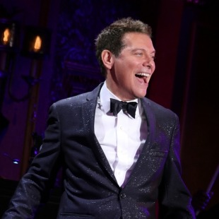 Man in a sparkling black tuxedo, white button down shirt and black bow tie smiling in front of a dark blue, purple and red background.