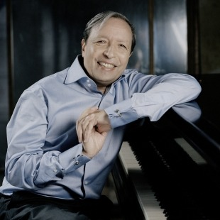 Murray Perahia in a button-down sitting at the piano in front of a black background.