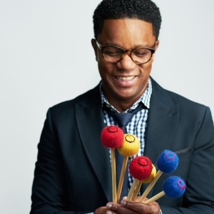 Man with glasses in a black tux, gingham button down and black tie holding red, blue and yellow vibraphone mallets in front of a light grey background.