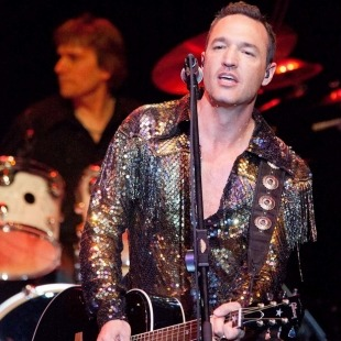 Image of a man in a gold sequin jacket playing a black guitar and singing in the microphone with a drummer behind him in front of a black background.