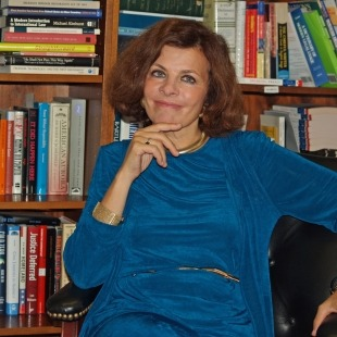 Photo of Nadine Strossen wearing a blue shirt sitting in front of a bookcase.
