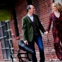 Image of the two performers from Celtic Celebration holding hands and their fiddles in cases while walking by a brick wall.