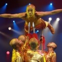 Man balancing on five spears being held by more men below him with stage lights in the background