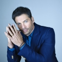 Harry Connick Jr wearing a blue blazer against a blue background.