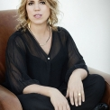 Image of Gabriela Monteri in a black shirt and pants seated on a brown chair.