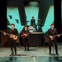 Image of the performers in RAIN on stage in black suits, white, shirts, and black ties in tribute to the early Beatles.