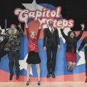 Six actors dressed in caricatures jumping in unison on stage in front of red, white, and blue background with Capitol Steps displayed overhead.