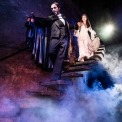 Phantom in white mask and black suite holding a lantern and leading Christine, who is wearing a white dress, down stone steps with a dark background and fog beneath them.