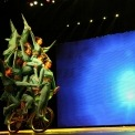 Eight acrobats wearing green costumes riding a single bicycle with a blue light background.