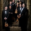 Image of the eight ukulele players holding their ukuleles and posed on steps smiling into the camera with stone walls behind them