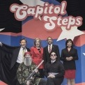 4 actors in caricature standing, 2 actors in caricature kneeling, all posing for a professional image in front of red, white, and blue background with Capitol Steps displayed overhead.