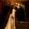 Christine in a white dress facing a mirror that shows the Phantom in black reaching out to her with fog in between them.