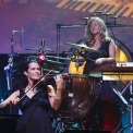 Woman playing a violin and another woman drumming behind her