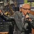 Paul Shaffer wearing a suit and singing into a microphone
