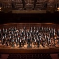 Image of the entire orchestra standing and smiling at the camera
