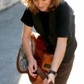 Susan Werner outside playing her guitar